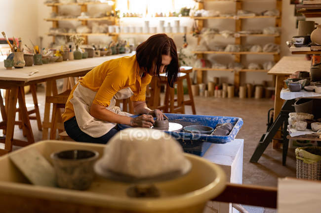Side view of a young Caucasian female potter sitting and working with clay on a potters wheel in a pottery studio, with equipment in the foreground — Stock Photo
