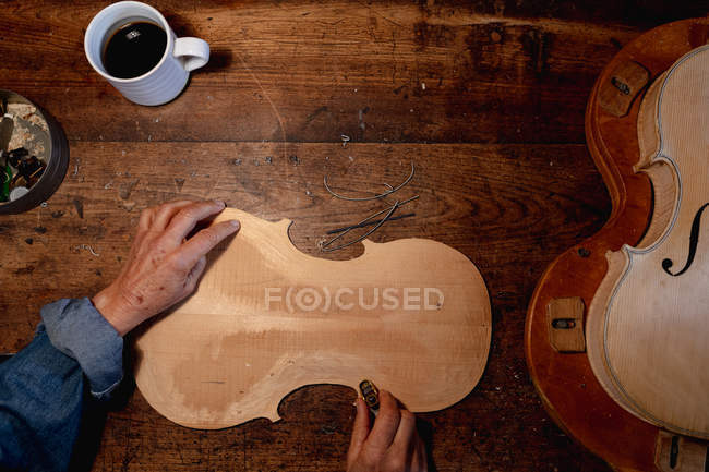 Overhead view of female luthier working on the body of a violin in her workshop, with coffee cup on a workbench — Stock Photo