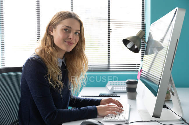 Side view close up of a young Caucasian woman sitting at a desk by a window using a computer, turning and smiling to camera in the modern office of a creative business — Stock Photo