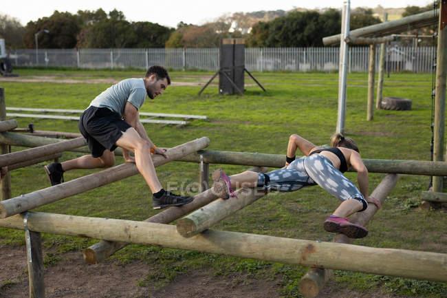 Vista lateral de una joven mujer caucásica y un joven caucásico trepando a través de vigas en un marco de escalada en un gimnasio al aire libre durante una sesión de entrenamiento de bootcamp - foto de stock