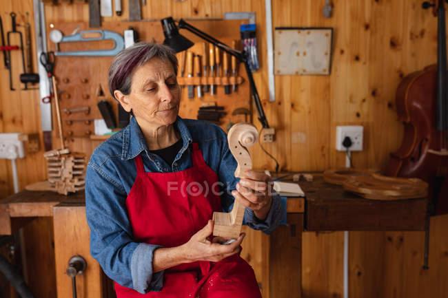 Вид спереди крупным планом старшей кавказки-лютирки, держащей свиток скрипки в мастерской, с инструментами, висящими на стене на заднем плане — стоковое фото