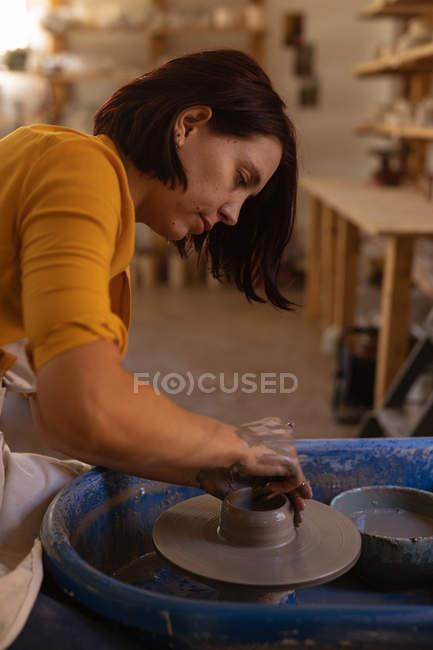 Vista lateral perto de uma jovem cerâmica caucasiana moldando barro molhado em um pote em uma roda de oleiros em um estúdio de cerâmica — Fotografia de Stock