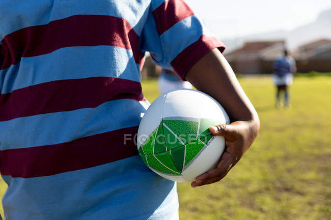 Front view mid section of female rugby player standing on a rugby pitch holding a rugby ball — Stockfoto