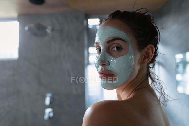 Вид сбоку на молодую брюнетку, одетую в пакет с лицом, разворачивающуюся, чтобы посмотреть в камеру в современной ванной комнате — стоковое фото