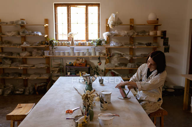 Side view of a young Caucasian female potter sitting at a work table painting a colored glaze on a clay flask in a pottery studio — Stock Photo