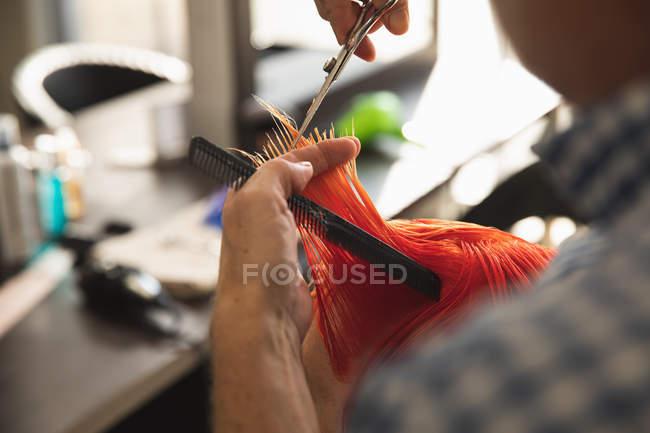 Primo piano di un parrucchiere caucasico di mezza età e di una giovane donna caucasica con i capelli colorati di rosso brillante e tagliati in un salone di parrucchiere — Foto stock