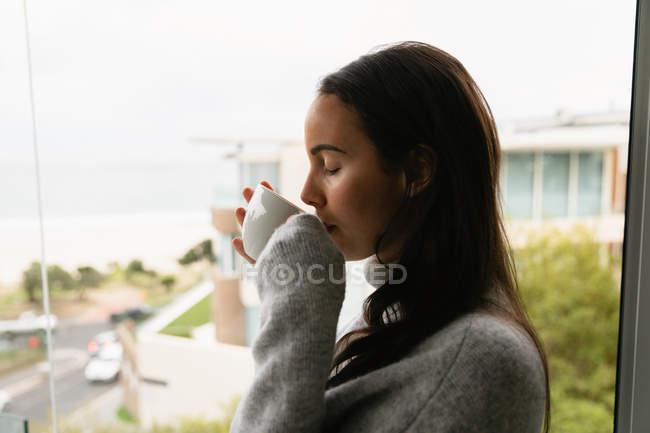 Вид збоку крупним планом молодий Кавказький жінка брюнетка одягнений в сірий светр водолазки, стоячи на вікна пити чашку кави з закритими очима — стокове фото