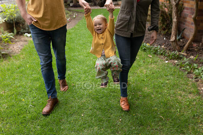 Front view of a low section of a young Caucasian father and mother holding hands with their baby and walking in a garden, swinging the baby — Stock Photo