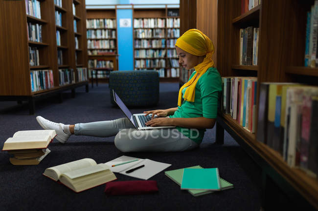 Vista lateral de cerca de una joven estudiante asiática usando un hijab usando una computadora portátil y estudiando en una biblioteca - foto de stock