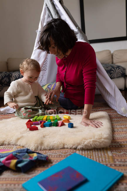 Front view close up of a young Caucasian mother playing with her baby on a floor, with a tent in a background — Stock Photo