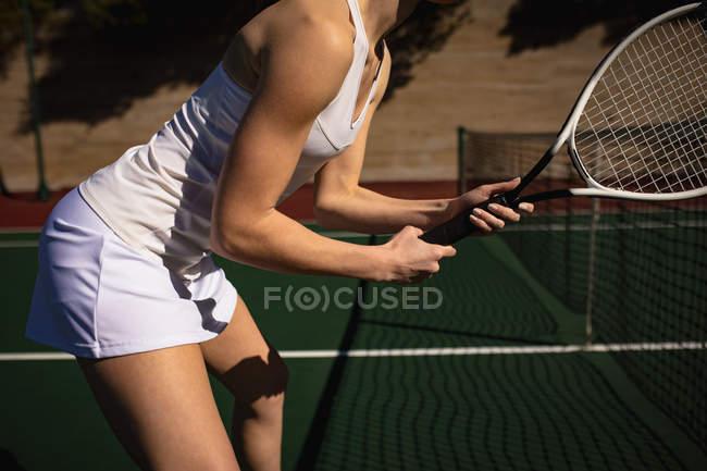 Vista lateral close-up da mulher jogando tênis em um dia ensolarado, segurando uma raquete e esperando a bola — Fotografia de Stock
