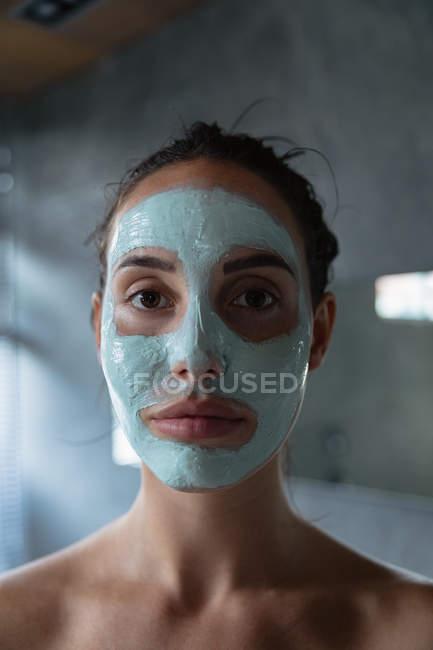 Porträt einer jungen kaukasischen Brünetten mit Gesichtsmaske, die in einem modernen Badezimmer direkt in die Kamera blickt — Stockfoto