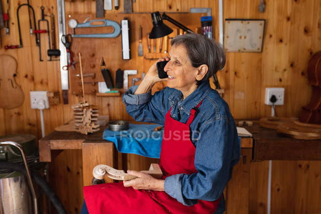 Side view of a senior Caucasian female luthier talking on the phone in her workshop with tools hanging up on the wall in the background — Stock Photo