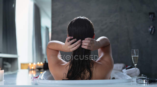 Rear view of a young Caucasian brunette woman sitting in a bath with lit candles and a glass of champagne on the side, adjusting her hair — Stock Photo