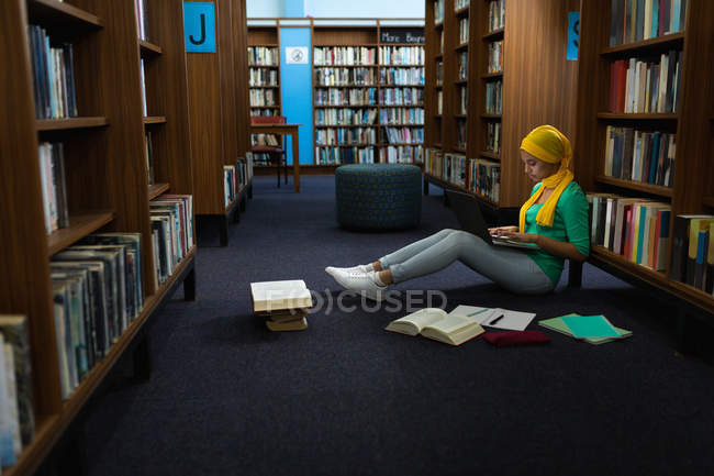Side view of a young Asian female student wearing a hijab using a laptop computer and studying in a library — Stock Photo