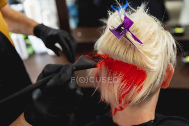 Vista posteriore primo piano di un parrucchiere caucasico di mezza età e di una giovane donna caucasica con i capelli colorati di rosso brillante in un salone di parrucchiere — Foto stock