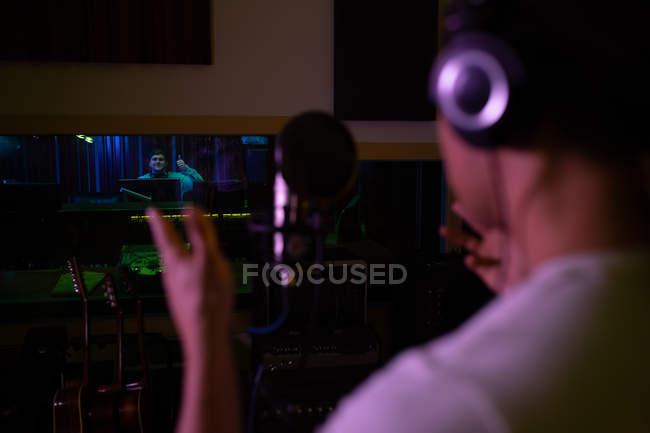 Sobre a vista do ombro de um jovem cantor misto vestindo fones de ouvido em frente a um microfone em uma sala de gravação — Fotografia de Stock