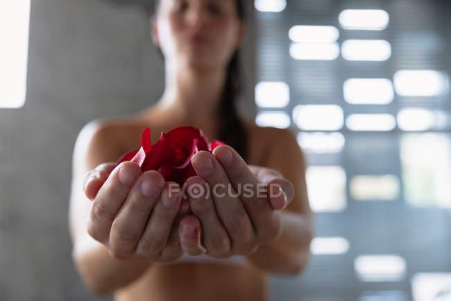 Vista frontal close-up de uma jovem mulher morena caucasiana com as mãos cochiladas segurando pétalas de rosa em um banheiro moderno, com foco no primeiro plano — Fotografia de Stock