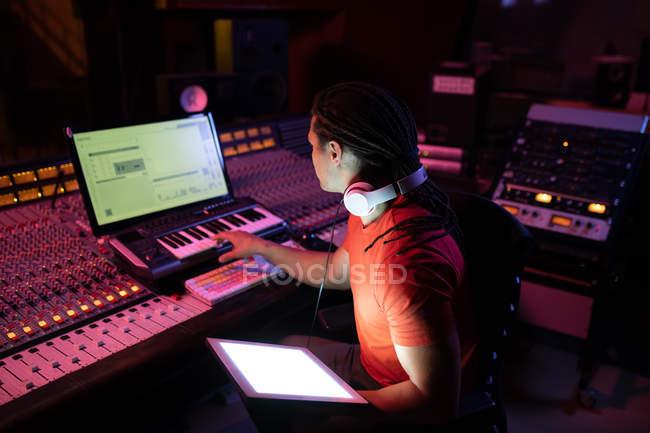 Vista laterale da vicino di un giovane ingegnere del suono maschio di razza mista seduto e che lavora presso un mixer in uno studio di registrazione utilizzando un computer e una tastiera midi controller — Foto stock