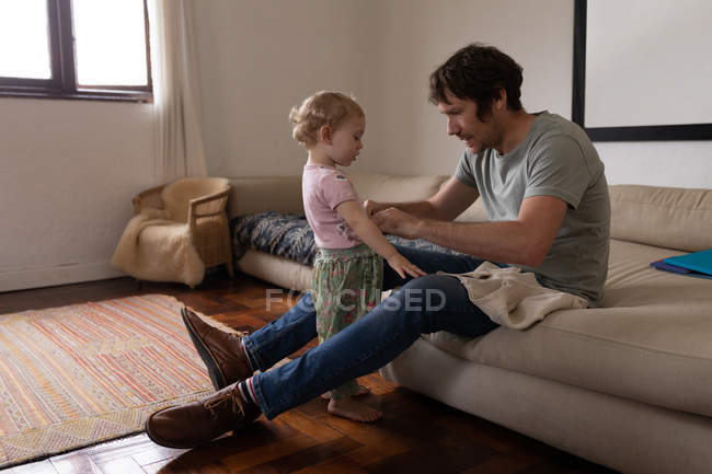 Side view of a young Caucasian father getting his baby dressed, sitting on a couch — Stock Photo