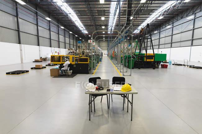 Vista lateral perto de um trabalhador de fábrica afro-americano sentado e operando equipamentos em um armazém em uma fábrica de processamento de plantas, com duas cadeiras e uma mesa com chapéus duros e um computador portátil em primeiro plano — Fotografia de Stock