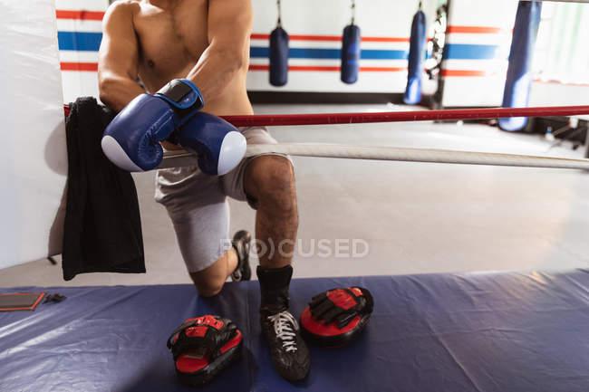 Спереди низкая секция боксера-мужчины на боксерском ринге, опирающаяся на спину — стоковое фото