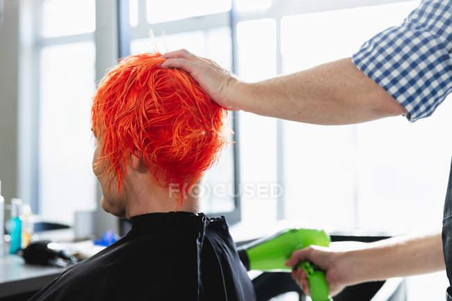 Vista posteriore primo piano del parrucchiere maschile e di una giovane donna caucasica con i capelli colorati di rosso brillante e asciugati in un salone di parrucchiere — Foto stock