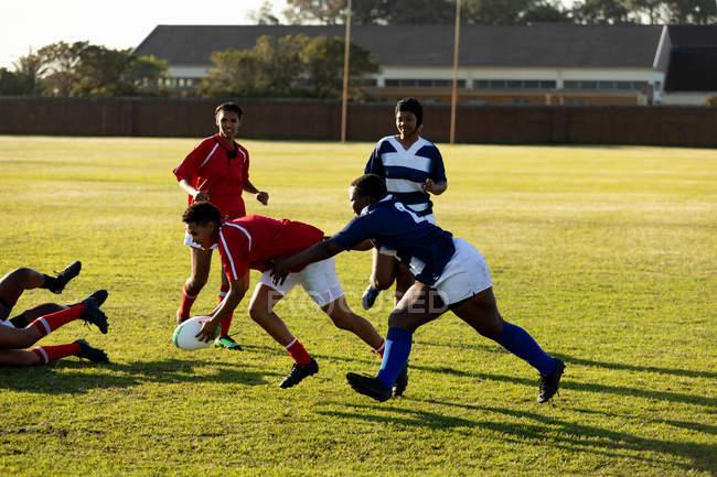 Сторона зору групи молодих дорослих багатоетнічних жінок регбі гравців під час матчу, з одним гравцем, який бігає з м'ячем — стокове фото