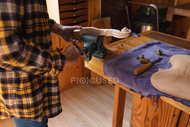 Seitenansicht einer Geigenbauerin, die die Rolle einer Geige in einen Schraubstock steckt — Stockfoto