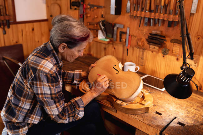 Side view of a senior Caucasian female luthier working on the body of a violin in her workshop, with a tablet computer in front of her and tools hanging up on the wall in the background — Stock Photo