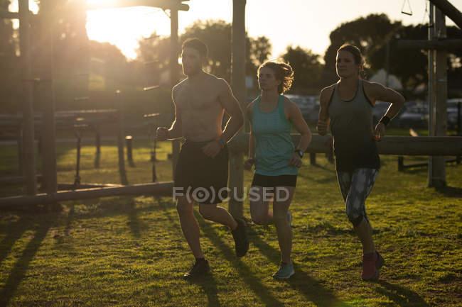 Vista frontale di due giovani donne caucasiche e di un giovane uomo caucasico che corre in una palestra all'aperto durante una sessione di allenamento bootcamp, retroilluminato dalla luce solare — Foto stock