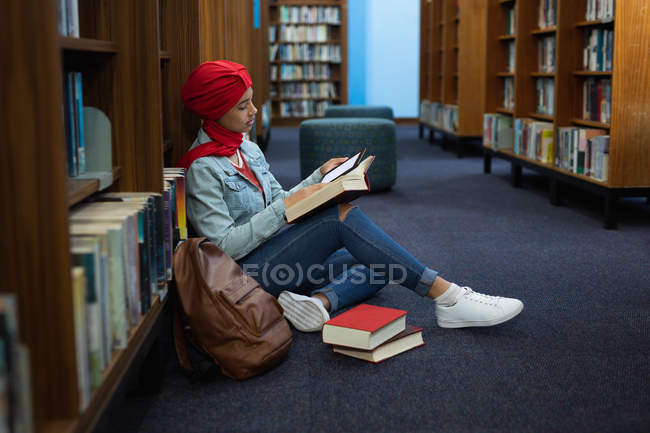 Vista laterale da vicino di una giovane studentessa asiatica che indossa un turbante mentre legge un libro e studia in una biblioteca — Foto stock