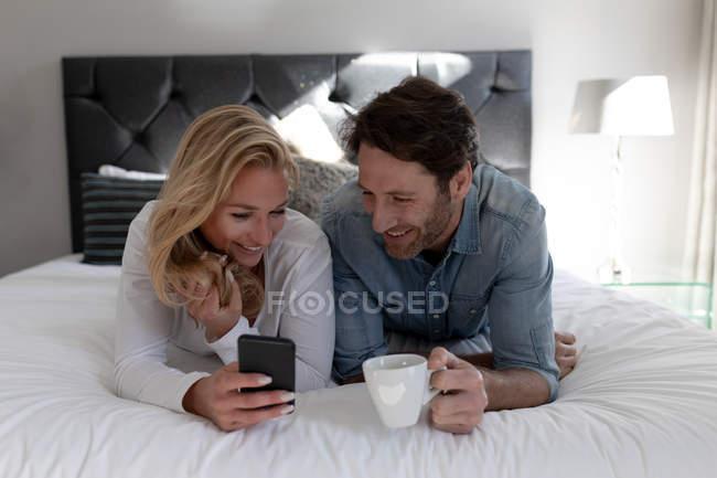 Vista dianteira de um par caucasiano novo feliz que relaxa junto no feriado em um quarto de Hotel que encontra-se em uma cama usando um smartphone — Fotografia de Stock