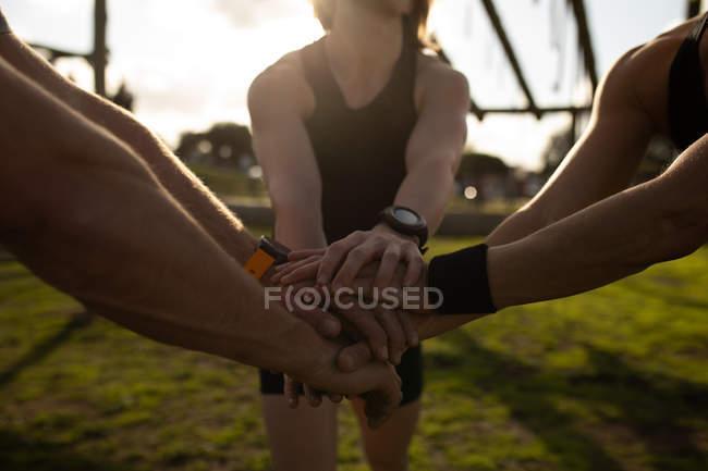 Vista frontal seção média de três adultos de pé juntos e empilhando as mãos em unidade em um ginásio ao ar livre durante uma sessão de treinamento de bootcamp — Fotografia de Stock