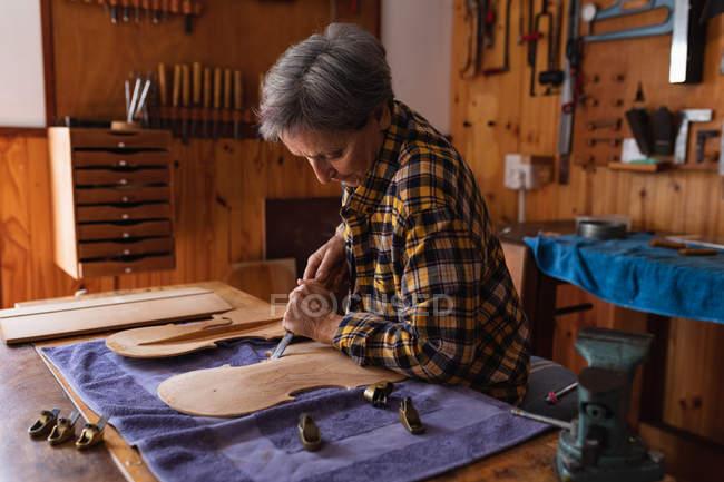 Vue latérale d'une luthière blanche senior travaillant sur le corps d'un violon dans son atelier avec des outils accrochés au mur en arrière-plan — Photo de stock
