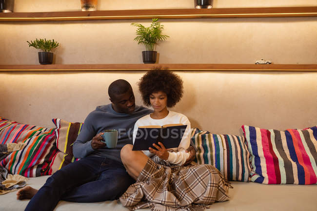 Front view of a young mixed race woman and a young African American man sitting on the sofa leaning on cushions looking at a book she is holding. — Stock Photo