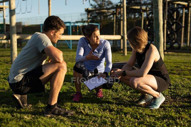 Vista frontal de uma jovem mulher caucasiana e um jovem homem caucasiano se agachando com uma jovem treinadora caucasiana segurando uma prancheta e conversando em um ginásio ao ar livre durante uma sessão de treinamento de bootcamp — Fotografia de Stock