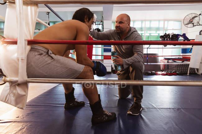 Seitenansicht von einem jungen Boxer mit gemischter Rasse, der in einem Boxring sitzt, während ein kaukasischer Trainer mittleren Alters seinen Kopf kühlt — Stockfoto