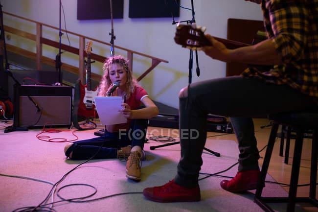 Vista frontal de uma jovem caucasiana sentada no chão cantando com um microfone e segurando letras enquanto um jovem mestiço sentado em um banquinho toca uma guitarra acústica — Fotografia de Stock