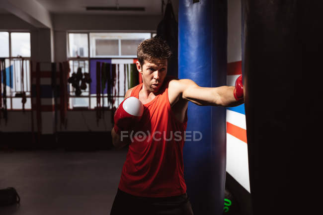 Front view close up of a young Caucasian male boxer in a boxing gym punching a punchbag — Stock Photo