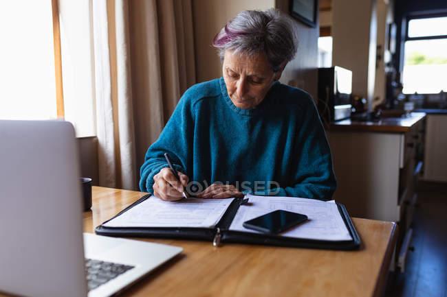 Vista frontale di una donna caucasica anziana seduta a un tavolo a casa a scrivere con uno smartphone e un computer portatile davanti a lei — Foto stock