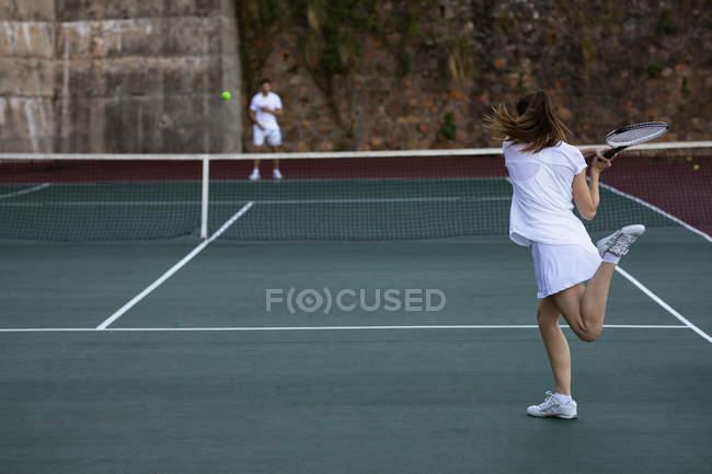 Visão traseira de uma jovem mulher caucasiana e um homem jogando tênis, mulher retornando a bola com uma parede no fundo — Fotografia de Stock