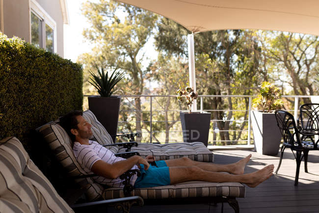 Side view of a young Caucasian man relaxing on holiday, reclining on a sunlounger — Stock Photo