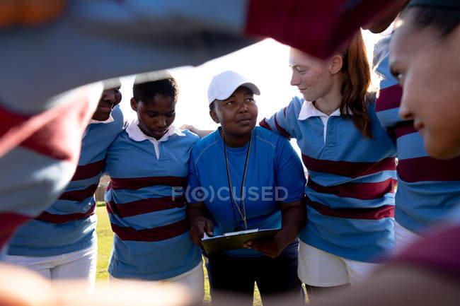 Au-dessus de l'épaule d'une équipe de jeunes joueuses de rugby multi-ethniques adultes debout sur un terrain de rugby avec les bras liés dans un huddle écouter leur entraîneur mixte d'âge moyen tout en se préparant pour un match de rugby — Photo de stock