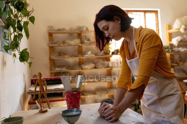 Seitenansicht einer jungen kaukasischen Töpferin, die an einem Arbeitstisch steht und in einem Töpferatelier ein Stück Ton knetet — Stockfoto