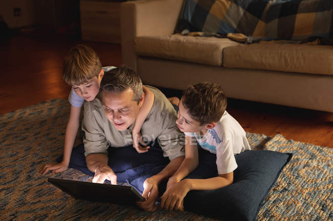 Front view of a middle aged Caucasian man and his pre teen sons using a laptop computer in a sitting room — Stock Photo