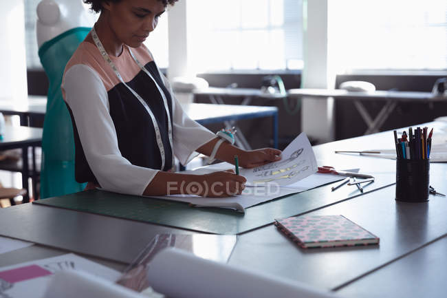Side view of a young mixed race female fashion student working on a design in a studio at fashion college — Stock Photo