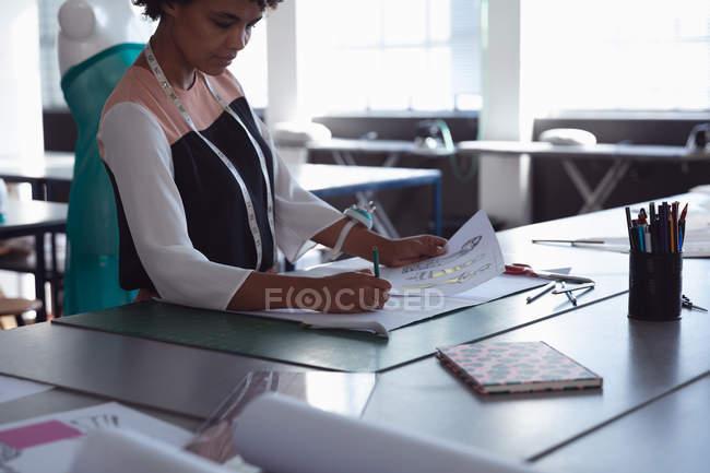 Вид сбоку молодой студентки-модницы смешанной расы, работающей над дизайном в студии при колледже моды — стоковое фото