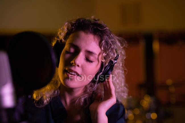 Vista frontal de perto de uma jovem cantora caucasiana usando fones de ouvido em frente a um microfone em um estúdio de gravação, com os olhos fechados — Fotografia de Stock
