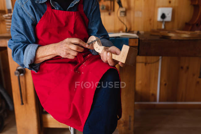 Front view close up of female luthier working on the scroll of a violin in her workshop — Stock Photo